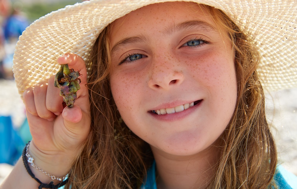 little smiling girl holds her hermit crab